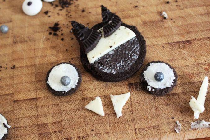 """Von Seite """"B"""" schneidet ihr die Hälfte der Creme runter. Daraus schneidet ihr die Zähnchen und etwas """"Kleber"""" für die Augen. Wenn ihr wollt, schneidet aus einem neuen Keks noch kleine Öhrchen und bringt diese an der Creme des Keks an. Wenn ihr Mini-Oreos habt, halbiert sie (beide Seiten sollten Creme haben) und setzt eine Zuckerperle drauf."""