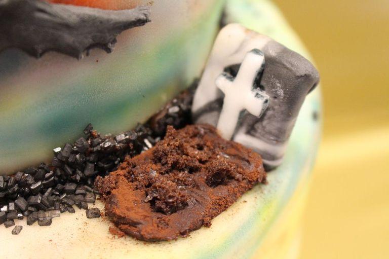Rest in Keks: Das Grab ist ein wenig Ganache mit Kakao und Kuchenkrümmeln sowie einem Keks, der mit weiß und schwarz vermischten Fondant überzogen ist.