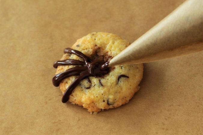 Mit der flüssigen Schokolade acht kleine Beinchen malen.
