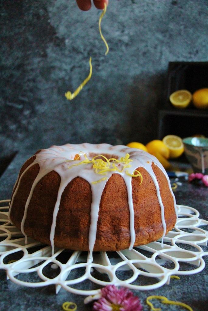 Zitronenzesten / Zitronenschalen fallen auf den Zitronenkuchen als Dekoration.